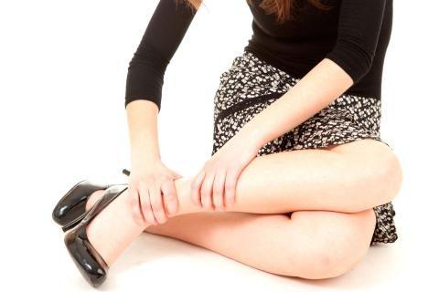 mujer aprieta con sus manos las piernas cansadas